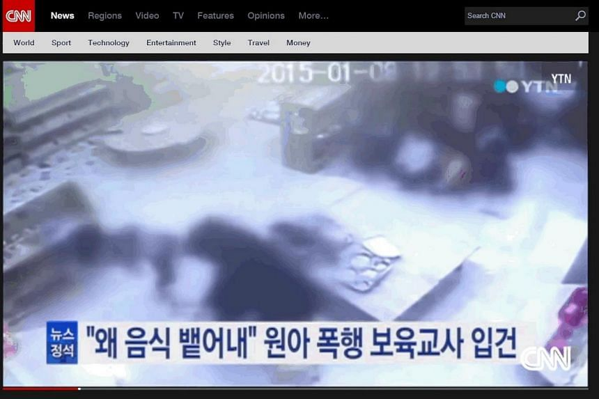 A toddler (left) being hit by a teacher in a South Korean nursery. -- PHOTO: SCREENGRAB FROM CNN.COM