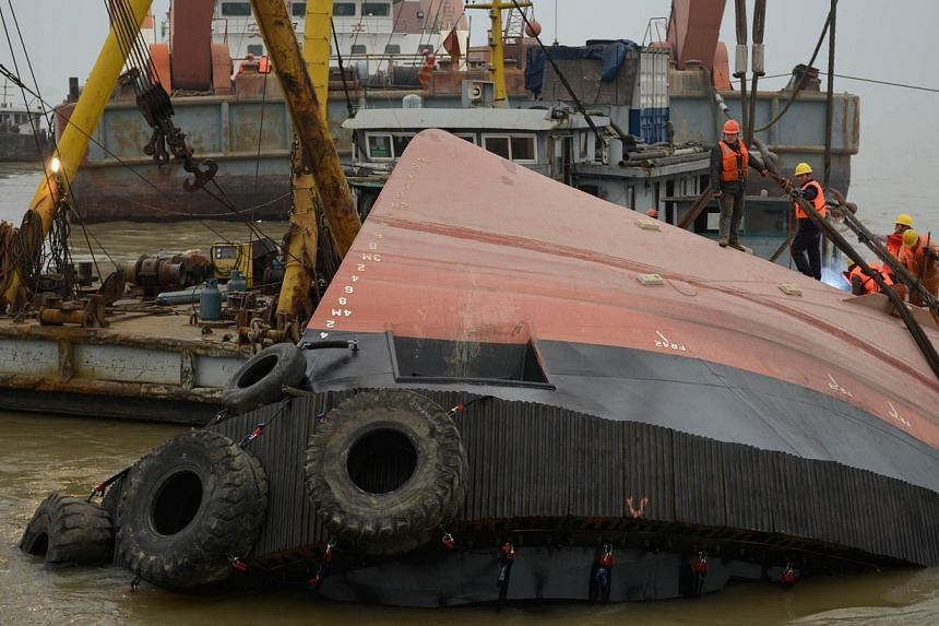 Members of a rescue team (orange) look at a section of the hull (front) of a tugboat which sank on a trial voyage in Jingjiang, east China's Jiangsu province, on Jan 16, 2015.Three of the people on board the tugboat that sank in China's Yangtze