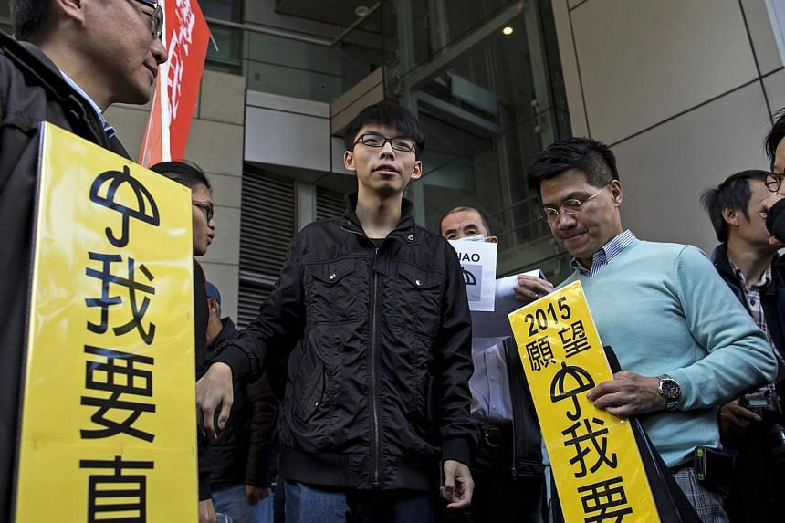 Student leader Joshua Wong (centre) being surrounded by supporters as he arrives at the police headquarters in Hong Kong on Jan 16, 2015. -- PHOTO: REUTERS