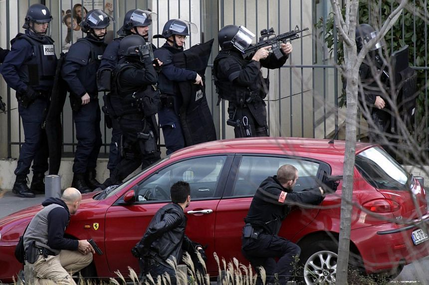 French Research and Intervention Brigades (BRI) policemen officers prepare near the post office where an armed man is holed up with two hostages on Jan 16, 2015, in Colombes, outside Paris, though there is no known link with last week's jihadist atta