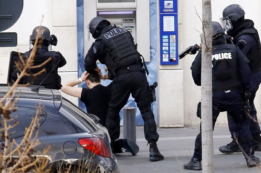 A man (kneeling), who had taken two hostages in a post office, is arrested by French Research and Intervention Brigades (BRI) police officers on Jan 16, 2015, in Colombes, outside Paris.-- PHOTO: AFP