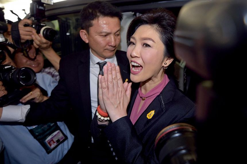 Ousted Thai prime minister Yingluck Shinawatra (centre) gestures a traditional greeting to members of the media in Bangkok on Jan 9, 2015. TheFormer Thai Prime Minister failed to appear at her second impeachment hearing on Friday, sending minis
