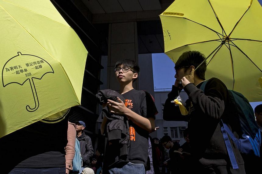 Hong Kong student leader Joshua Wong (centre), 18, is surrounded by supporters holding yellow umbrellas as he arrives at the police headquarters in Hong Kong on Jan 16, 2015. -- PHOTO: REUTERS