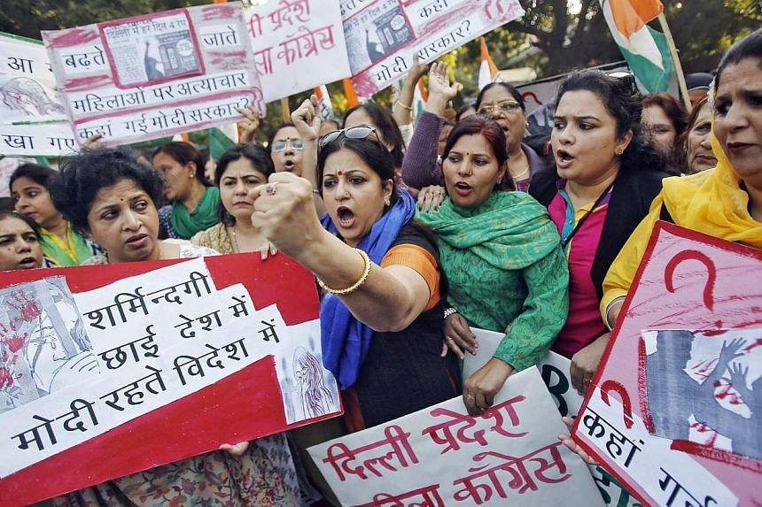 Members of All India Mahila Congress, women's wing of Congress party, shout slogans and carry placards during a protest against the rape of a female passenger, in New Delhi on Dec 8, 2014. The passenger has hired a prominent lawyer to sue the o