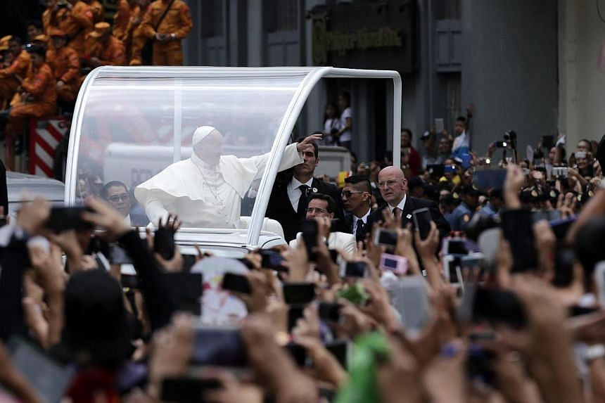 Pope Francis (centre), riding on a 'Popemobile', waves to Filipino well wishers at a street to lead a mass at the Manila cathedral, in Manila, Philippines on Jan 16, 2015. -- PHOTO: EPA