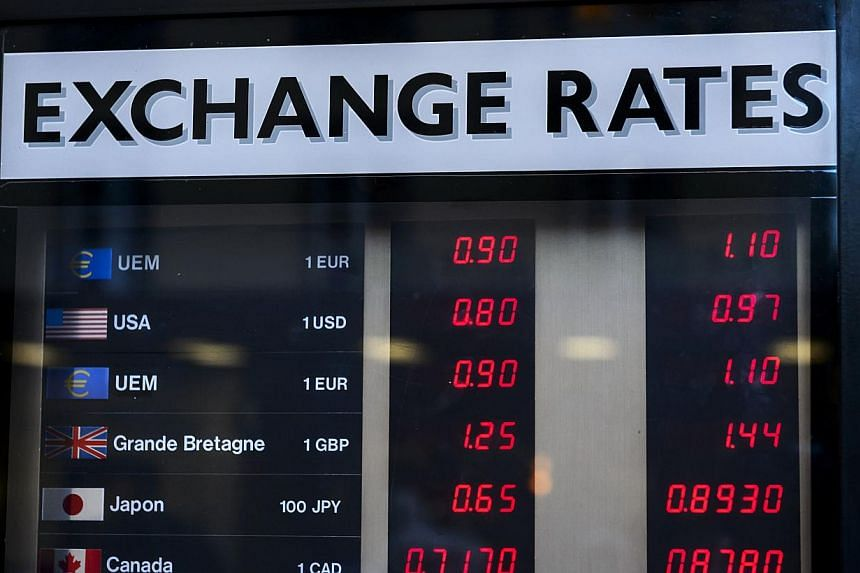 Currency rates displayed at an exchange office in Geneva on Jan 15, 2015. -- PHOTO: AFP