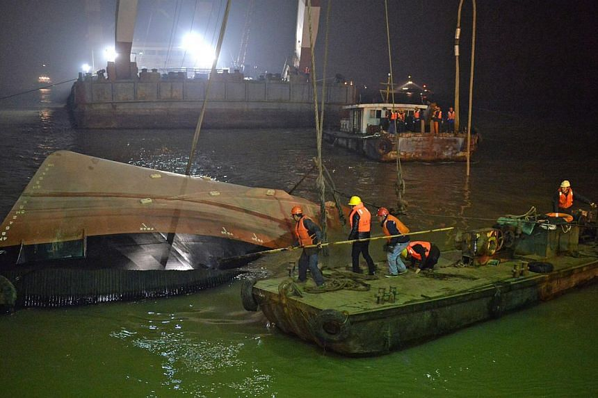 Salvage workers raising the tugboat on in the early hours of Jan 16, 2015. Twenty people, including Singaporeans and Japanese, are reported missing. -- PHOTO: XINHUA