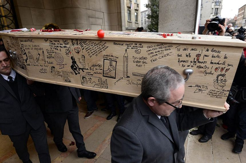 """The coffin of cartoonist Bernard """"Tignous"""" Verlhac, 57, one of the 12 people killed in the Jan 7 attack on French satirical weekly Charlie Hebdo, being carried out of the town hall of Montreuil, near Paris, during his funeral on Jan 15, 2015. -- PHOT"""