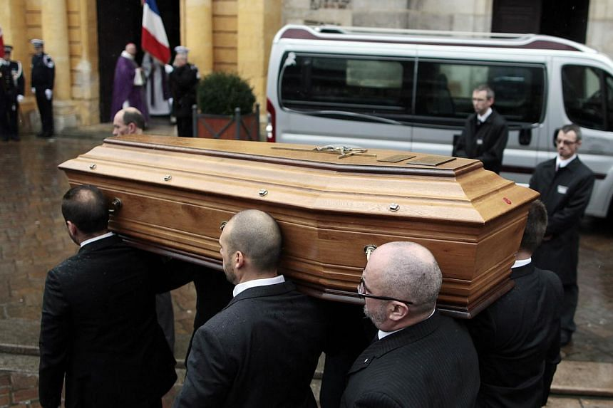 """Relatives of Franck Brinsolaro, the police officer charged with protecting late Charlie Hebdo editor Stephane Charbonnier, or """"Charb"""", carry his coffin into the Sainte-Croix Church for his funeral on Jan 15, 2015 in the northwestern French town of Be"""