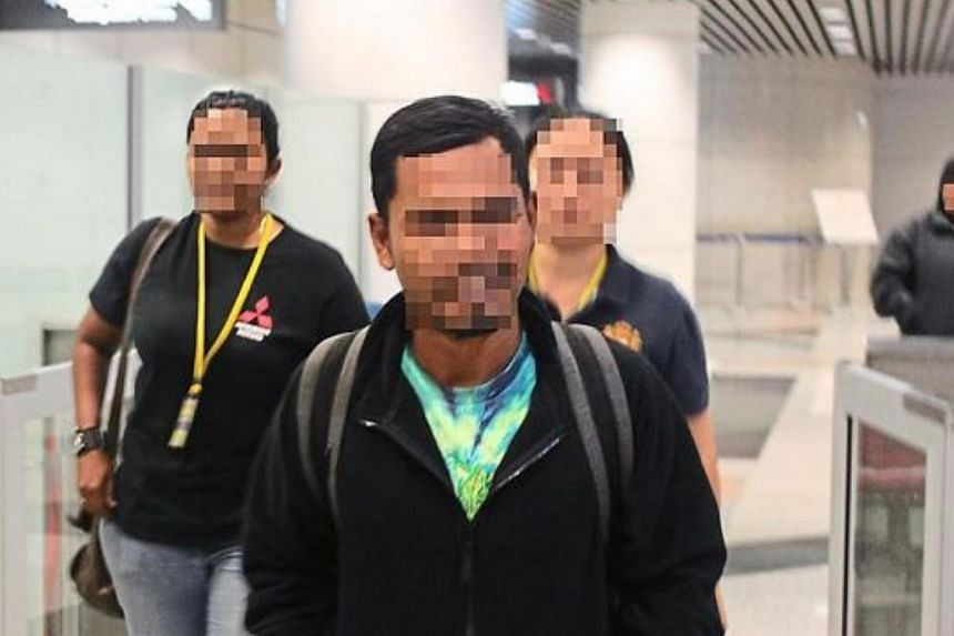 Counter Terrorism Division officers detained the suspect (centre) at KL airport on his arrival in Malaysia. -- PHOTO: THE STAR/ASIA NEWS NETWORK