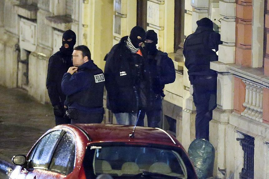 Belgian police enter a building in Palais street, near Colline street in Verviers, eastern Belgium, on Jan 15, 2015, as police set a large security perimeter around number 6 of Colline street where two men were reportedly killed during an anti-terror