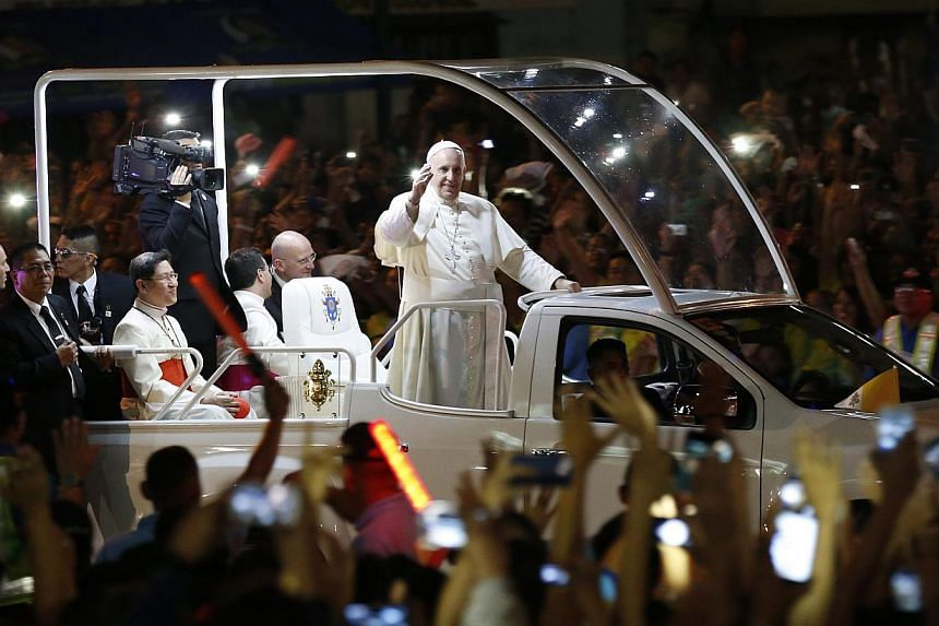 Pope Francis (centre) riding on a 'popemobile' waves to Filipino well wishers in Manila on Thursday. --PHOTO: EPA
