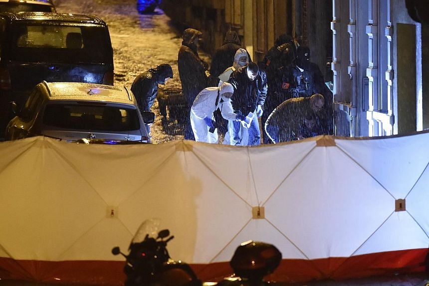 Policemen and forensic police work in the rain to a marked out perimeter in Colline street in Verviers, eastern Belgium, on Jan 15, 2015, after two men were reportedly killed during an anti-terrorist operation. -- PHOTO: AFP