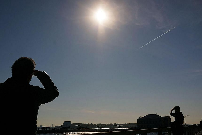 People relax along the water in lower Manhattan on a sunny afternoon which saw temperatures hit unseasonal highs on Nov 10, 2014 in New York City.Last year was the hottest in modern history, according a report by US government scientists on Fri