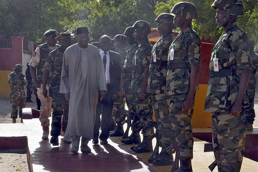 President Goodluck Jonathan (centre left) inspects a guard of honour by soldiers of the 7 Division of the Nigerian Army fighting Boko Haram terrorists during a surprise visit in Maiduguri on Jan 15, 2015. Nigeria's Mr Jonathan met survivors from what
