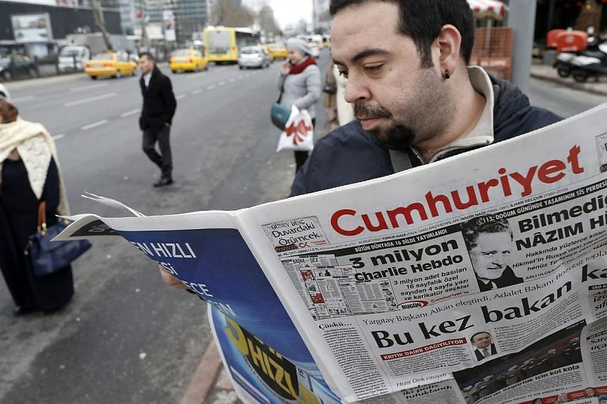 A Turkish man reads an edition of the Cumhuriyet daily newspaper featuringa four-page Charlie Hebdo pull-out translated into Turkish including cartoons satirising Nigerian Islamist group Boko Haram and Islamic State in Iraq and Syriain Is