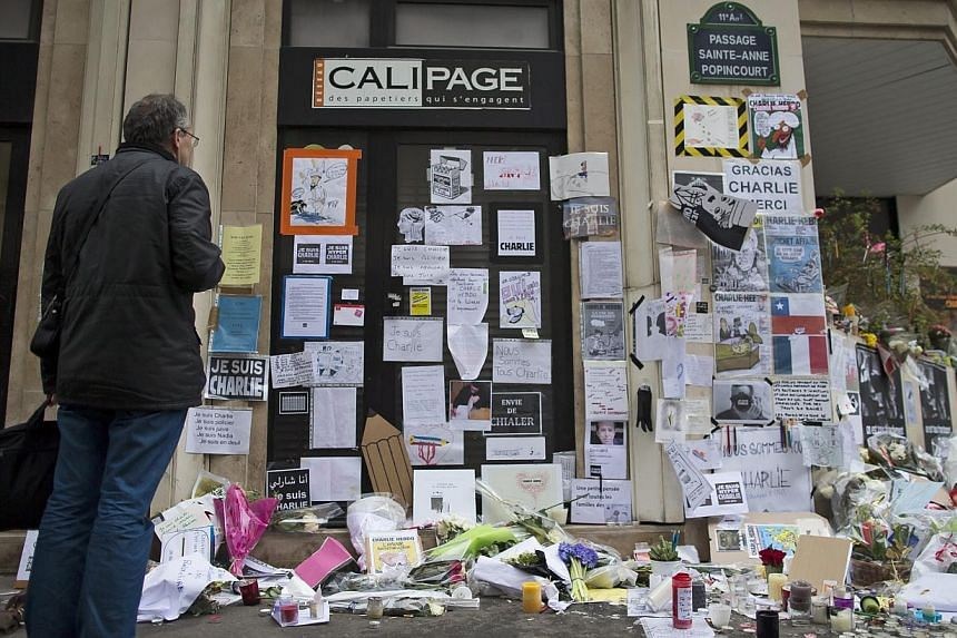 A man pays his respects next to the 'Charlie Hebdo' offices in Paris, France, on Jan 13, 2015. -- PHOTO: EPA