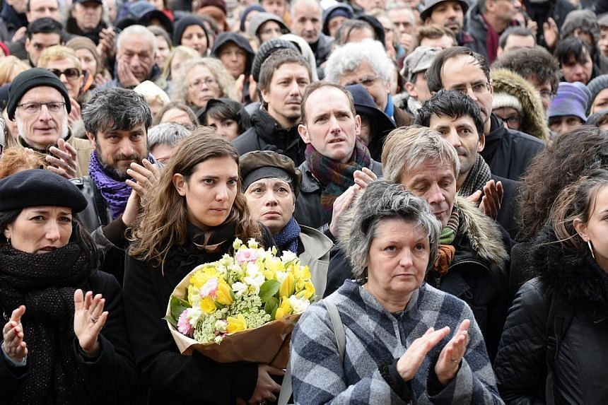 """People applaud during the funeral of Bernard """"Tignous"""" Verlhac, 57, one of the French satirical weekly Charlie Hebdo's cartoonists, on Jan 15, 2015, outside the town hall of Montreuil, near Paris. -- PHOTO: AFP"""