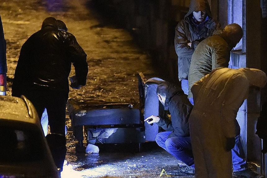 Policemen and forensic police work into a marked out perimeter in Colline street in Verviers, eastern Belgium, on Jan 15, 2015, after two men were reportedly killed during an anti-terrorist operation. -- PHOTO: AFP