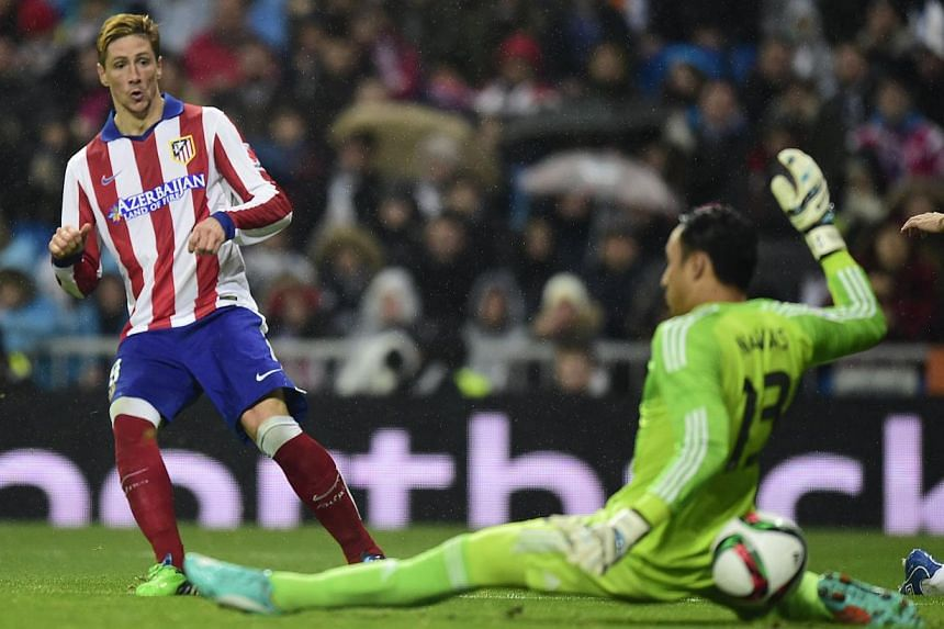 Atletico Madrid's forward Fernando Torres (left) scores during the Spanish Copa del Rey (King's Cup) round of 16 second leg football match Real Madrid CF vs Club Atletico de Madrid at the Santiago Bernabeu stadium in Madrid on Jan 15, 2015. -- PHOTO: