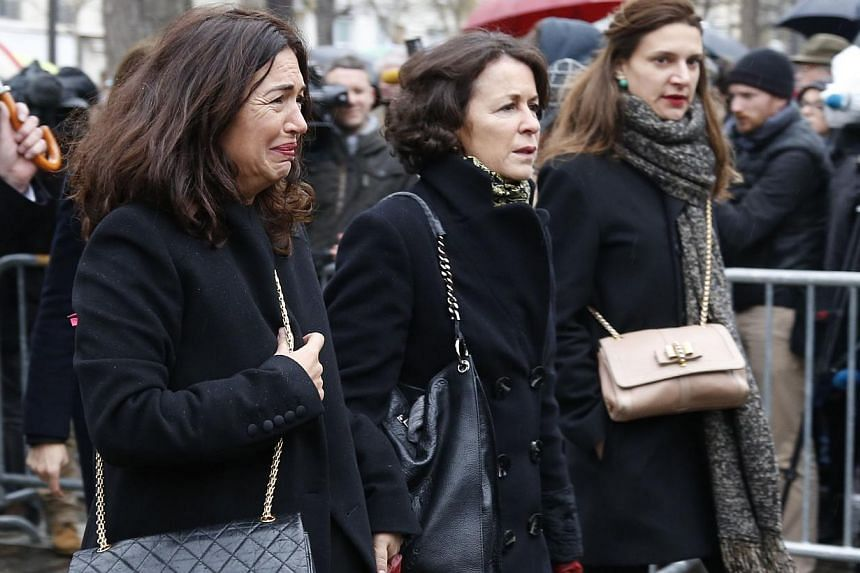 Elsa Wolinski (left), the daughter of Georges Wolinski, one of the French satirical weekly Charlie Hebdo's best-known cartoonists, arrives for the funeral of her father on Jan 15, 2015 at the Montparnasse cemetery in Paris. -- PHOTO: AFP