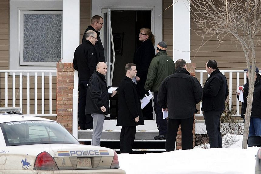 Investigators stand at the door to a home where a suspect who is reported to have shot two Royal Canadian Mounted Police (RCMP) officers at the Apex Casino ended his escape effort, near St. Albert, Alberta on Jan 17, 2015. -- PHOTO: REUTERS