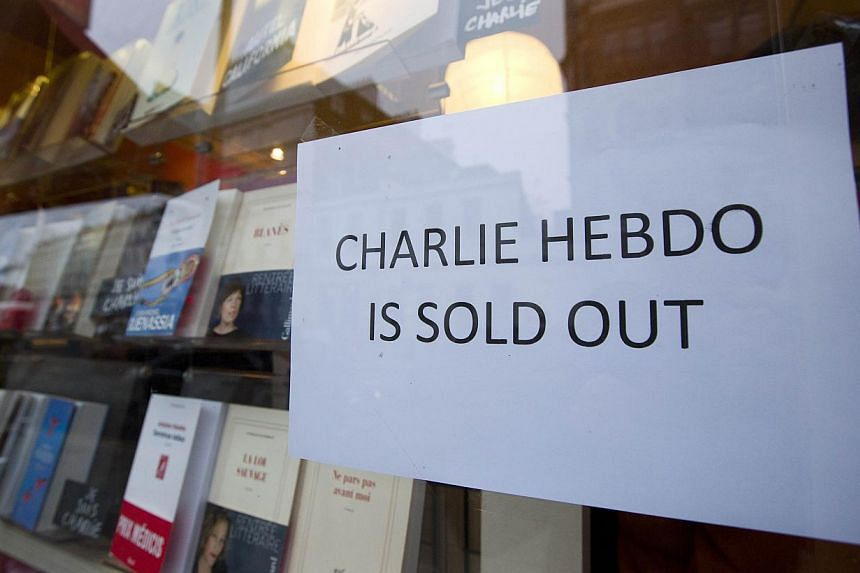 """A sign that reads """"Charlie Hebdo Is Sold Out"""" is seen in the window of a French book shop, earlier selling the satirical magazine Charlie Hebdo, in London on Jan 16, 2015. The chief editor of Charlie Hebdo has defended the satirical magazine's contro"""