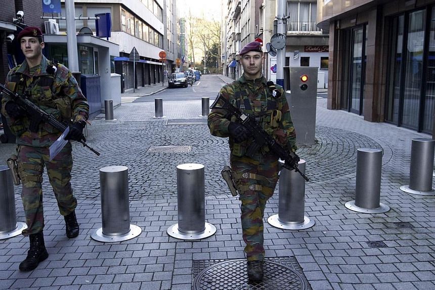 "Belgian soldiers patrol in Antwerp on Jan 17, 2015 after security forces smashed a suspected Islamist ""terrorist"" cell planning to kill police officers. The suspected mastermind of the extremist cell dismantled in Belgium remains at large, a Bel"