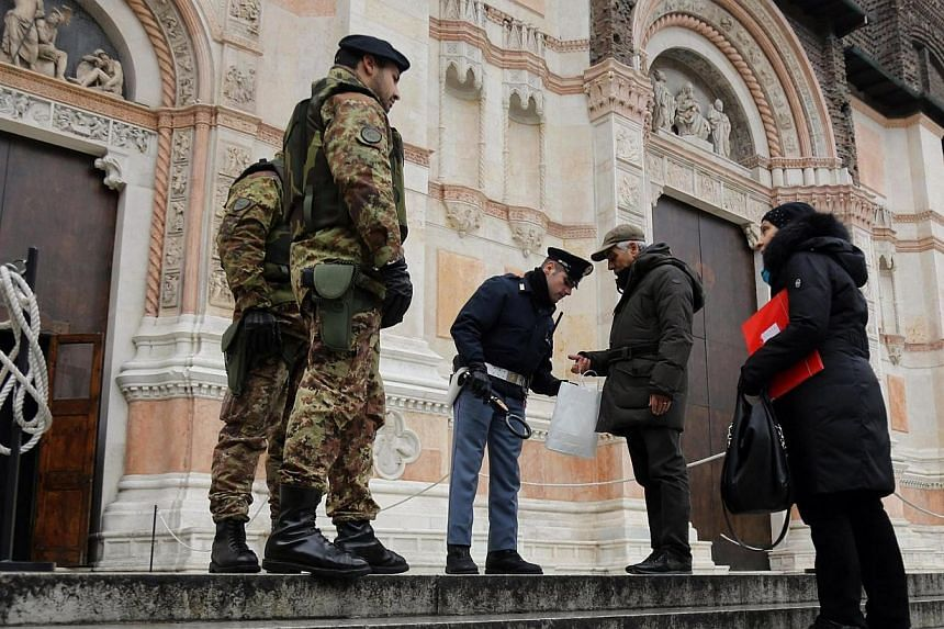 Security personnel check people with metal detectors at the entrance of San Petronio Basilica in Bologna, northern Italy, on Jan 16 2015. Italy has expelled nine suspected Islamist militants so far this year as part of a heightened security aler