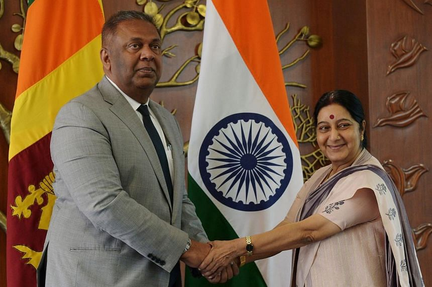 Sri Lankan Foreign Minister Mangala Samaraweera (left) and Indian Foreign Minister Sushma Swaraj shake hands before a meeting in New Delhi on Jan 18, 2015. Sri Lanka's new foreign ministermet his Indian counterpart in New Delhi on Sunday during