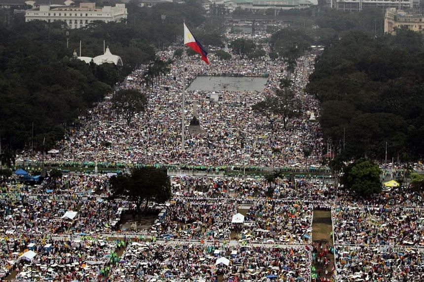 A handout photo provided by the Philippine Air Force Public Information Office (PAF-PIO) shows aerial shot of devotees during a downpour of rain waiting for the arrival of Pope Francis to celebrate a mass at the Rizal park in Manila, Philippines, on