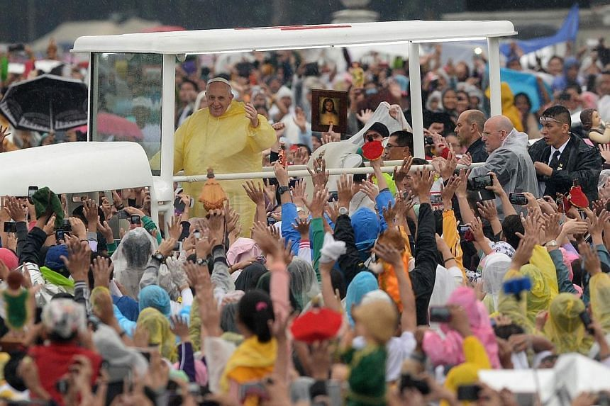 Pope Francis (top left) greets worshippers as he arrives to celebrate a mass at Rizal park in Manila on Jan 18, 2015. Pope Francis celebrated an open-air mass for millions of rain-soaked worshippers on Sunday, capping his dramatic five-day visit in A