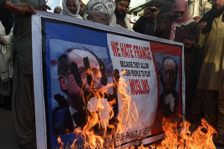 Pakistani protesters burn a poster featuring a portrait of French President Francois Hollande during a protest against the printing of satirical sketches of the Prophet Muhammad by French magazine Charlie Hebdo, in Quetta on Jan 18, 2015.Thousands of
