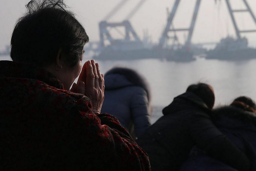 A relative prays on the river bank during search and rescue operations on an overturned tugboat in the Yangtze River, Jingjiang city, Jiangsu province, China, on Jan 17 2015. -- PHOTO: EPA