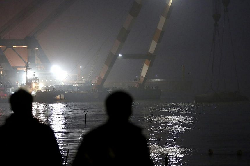 People watch a floating crane during recovery operations for a sunken tugboat on the Yangtze River in Jingjiang city, China's Jiangsu province, on Jan 16 2015. -- PHOTO: EPA