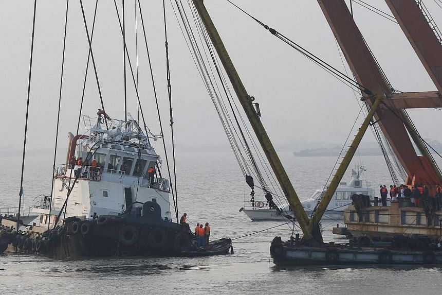 Search and rescue team operate on an overturned tugboat in the Yangtze River, Jingjiang city, Jiangsu province, China, on Jan 17 2015. Before Mr Baginda Ali Zainul Abiddin flew to China for work, his family was worried about his flight there, gi