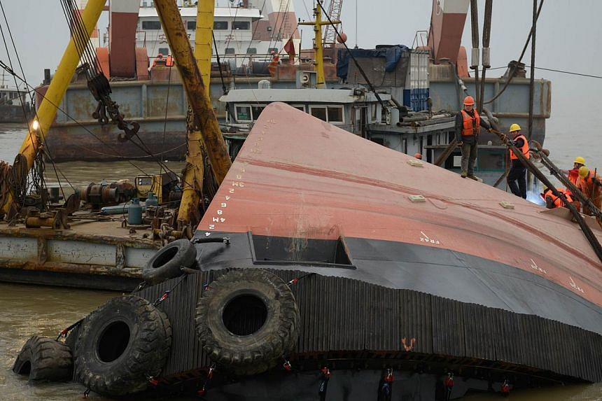 Members of a rescue team (orange) look at a section of the hull (front) of a tugboat which sank on a trial voyage in Jingjiang, east China's Jiangsu province on Jan 16, 2015. -- PHOTO: AFP