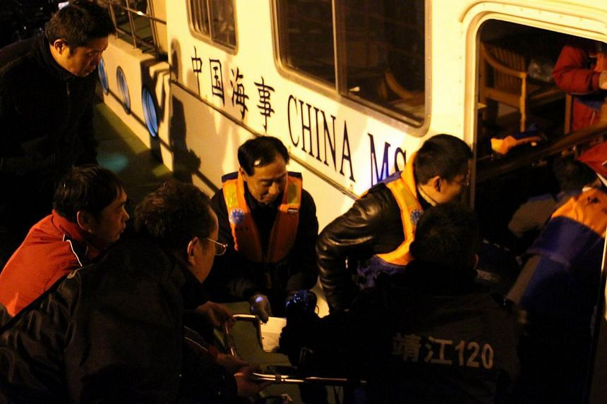 Members of a rescue team bring a survivor onboard after a tugboat sank in Jingjiang, east China's Jiangsu province on Jan 16, 2015. -- PHOTO: AFP