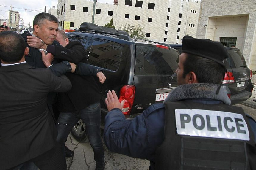 Members of Palestinian security forces and a policeman hold back a protester after eggs were thrown at Canada's Foreign Minister John Baird, during his visit to the West Bank city of Ramallah on Jan 18, 2015. Palestinian protesters heckled and t
