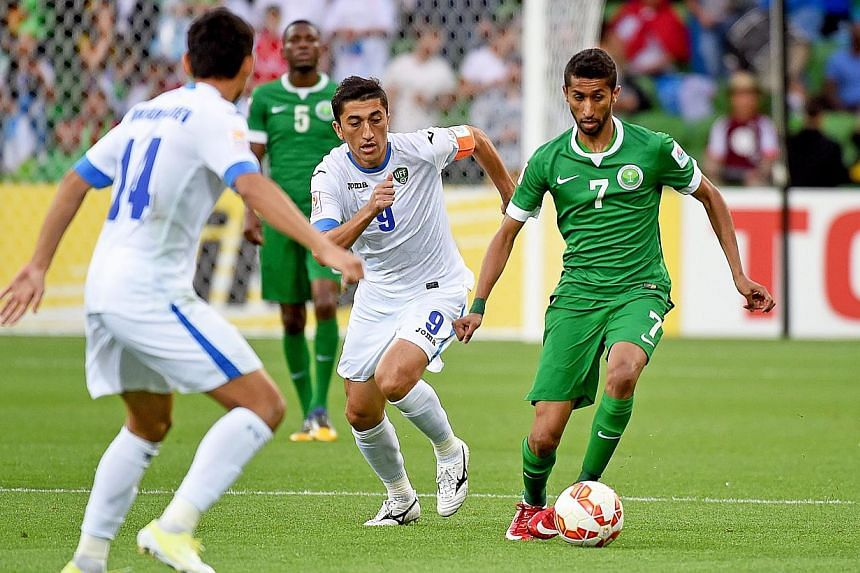 Salman Alfaraj (right) of Saudi Arabia in action against Odil Akhmedov (centre) of Uzbekistan during their AFC Asian Cup Group B soccer match at the Melbourne Rectangular Stadium in Melbourne, Australia on Jan 18, 2015.Uzbekistan booked a place