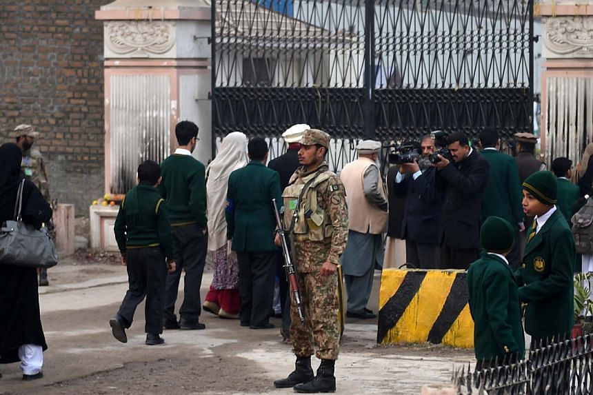Pakistani soldiers stand guard as parents arrive with their children at the Army Public School in Peshawar on Jan 12, 2015.Five Pakistani men have been arrested in Afghanistan in connection with the Taleban massacre of 134 school children at th