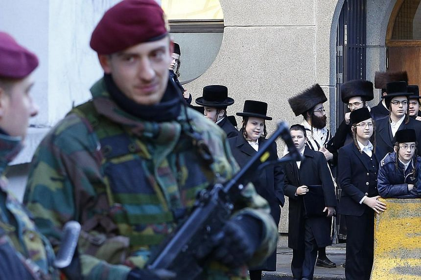 Belgian paratroopers keep guard outside a Jewish school in central city of Antwerp on Jan 17, 2015.The arrests of at least four people by Greek anti-terrorism police are not linked to a probe into a militant cell broken up this week in Belgium,