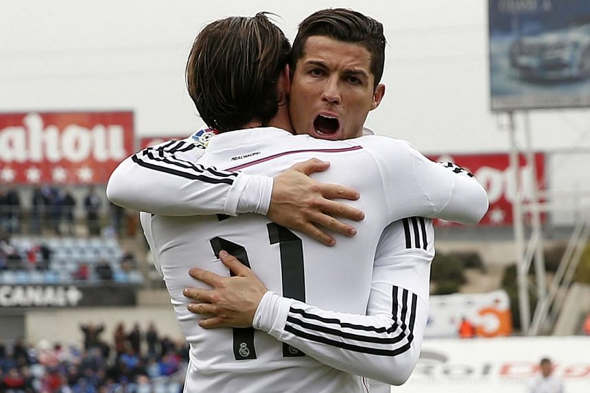 Real Madrid's Cristiano Ronaldo (right) congratulates his teammate Gareth Bale after scoring a goal against Getafe during their Spanish first division soccer match at Colisseum Alfonso Perez stadium in Getafe, outside Madrid on Jan 18, 2015. Cri