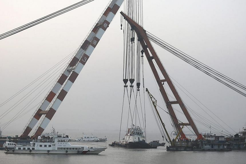 Search and rescue teams working on the tugboat which has been lifted from the waters. It sank in the Yangtze River last Thursday. (Above, right) Rescue workers yesterday transporting on a barge the covered bodies of the victims. Twenty-two people die