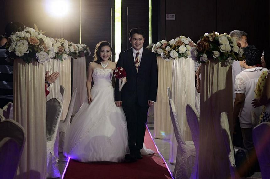 Newlyweds Gideon Tan and Rebecca Goh (both above) held their wedding at Pekin Restoran Johor Jaya restaurant in Johor Baru and chartered two buses to the tune of $1,400 to ferry their family and friends across the Causeway. --PHOTO: COURTESY OF