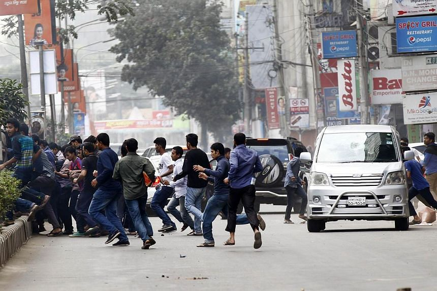 Bangladeshi activists run across a road close to the home of opposition leader Khaleda Zia in Dhaka on Jan 5, 2015. Bangladeshi telecoms authorities on Sunday, Jan 18, shut down smartphone messaging services Viber and Tango, which had become a p