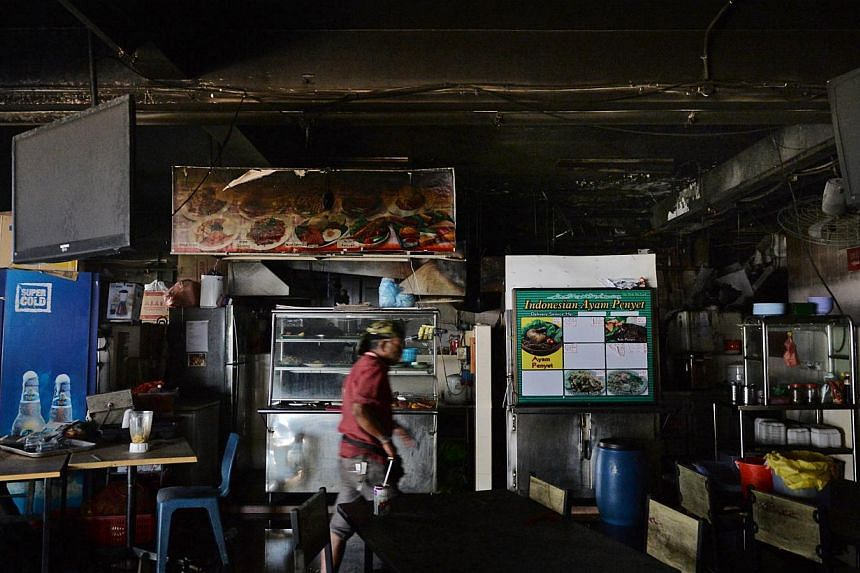 A man walking in Good Good's Eating house after the fire was put out, on Jan 18, 2015.-- ST PHOTO:CAROLINE CHIA