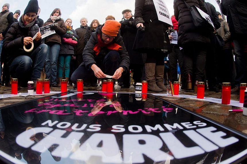People gather to express solidarity for the victims of the attack on the French satirical magazine 'Charlie Hebdo' on the Opernplace in Hanover, Germany on Jan 11, 2015.The attacks in Paris and the radical Islamist cell dismantled in Brussels h