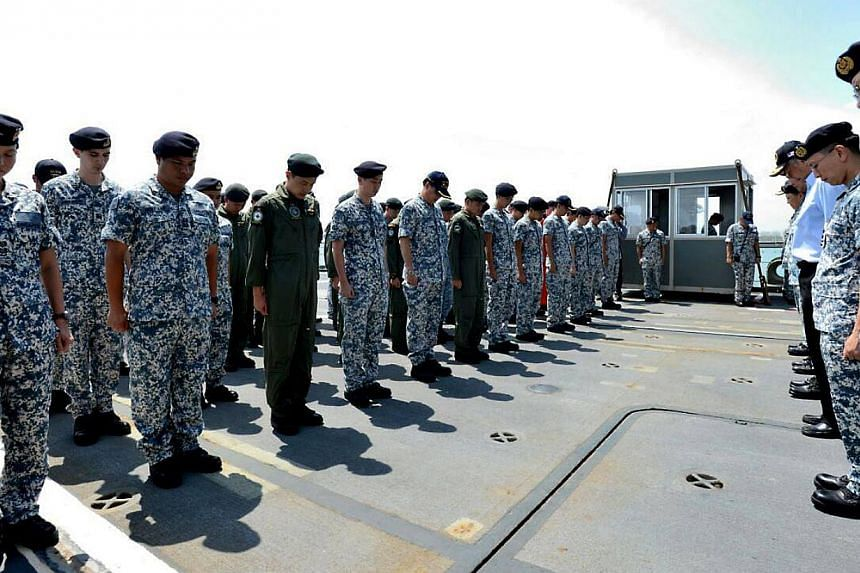 Defence Minister Ng Eng Hen and members of the search operation observing a minute of silence for the victims of the AirAsia crash.-- PHOTO: NG ENG HEN/FACEBOOK