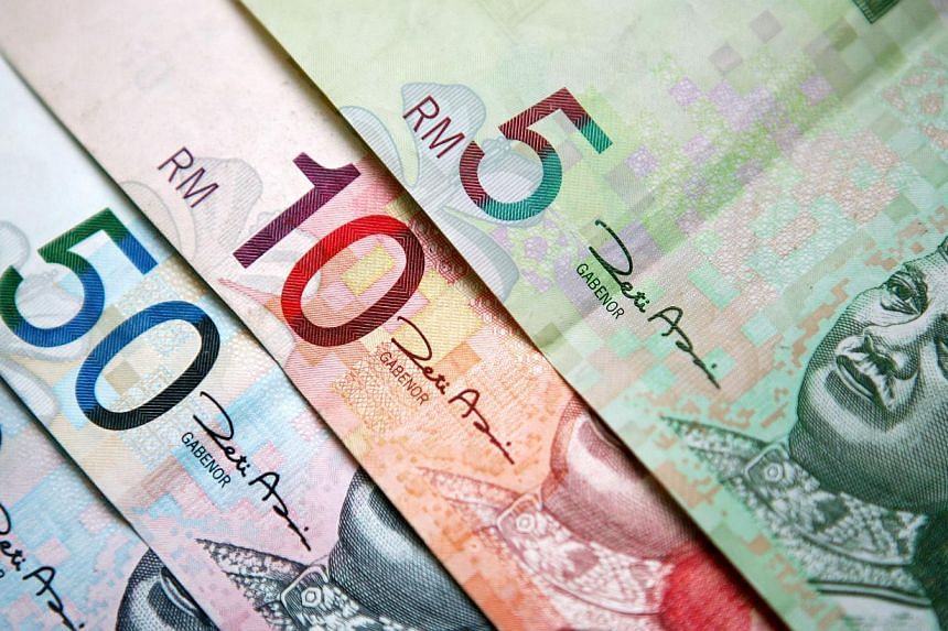 Malaysia's ringgit extended a three-month loss to almost 10 per cent, the worst in Asia, after the government's increase to the fiscal deficit target prompted Fitch Ratings to warn of a credit-rating downgrade. -- PHOTO: BLOOMBERG